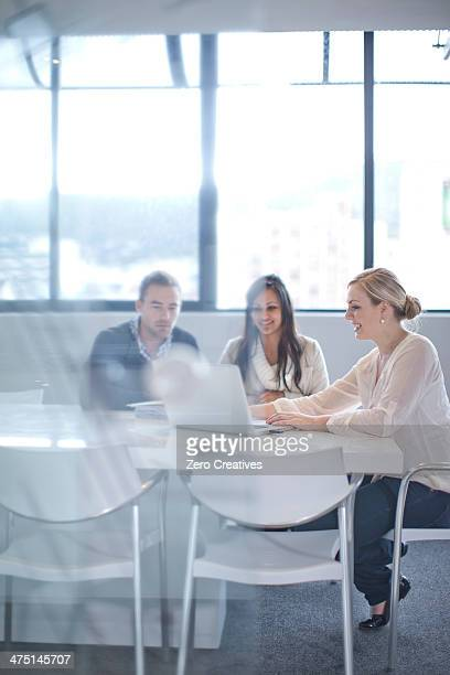 Businesspeople sitting at conference table looking at laptop
