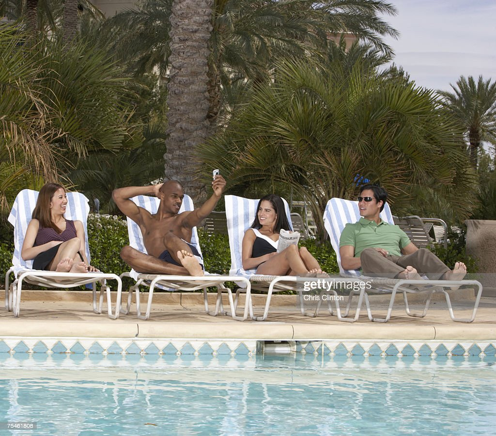 Businesspeople sitting at poolside, man photographing self with mobile phone : Stock Photo