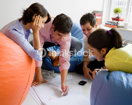 Businesspeople sitting in bean bag chairs and watching businessman write : Stock Photo
