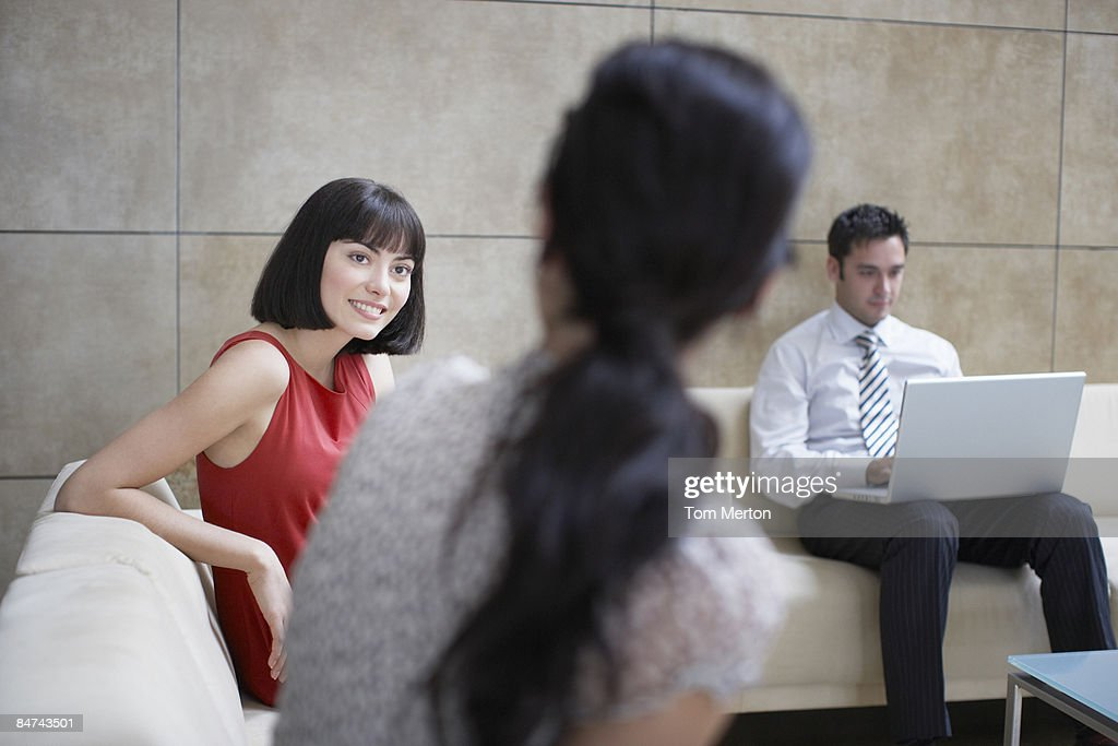 Businesspeople sitting in office lobby : Stock Photo