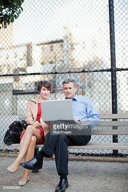 Businesspeople sitting on bench using laptop