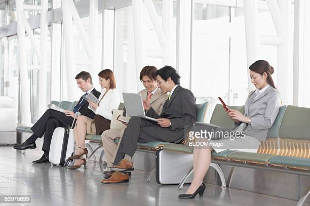 Businesspeople sitting on bench, using PC and cellular phone, reading newspaper, taking notes