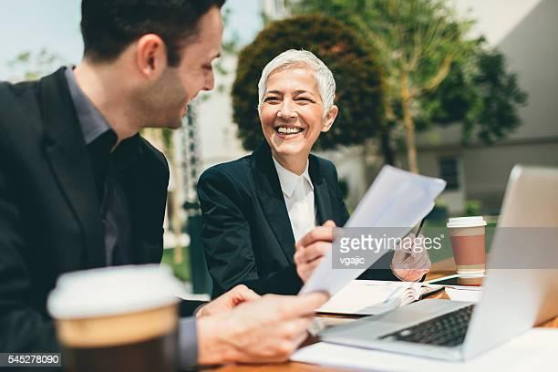 Hommes d'affaires assis en plein air et se servant d'un ordinateur portable.