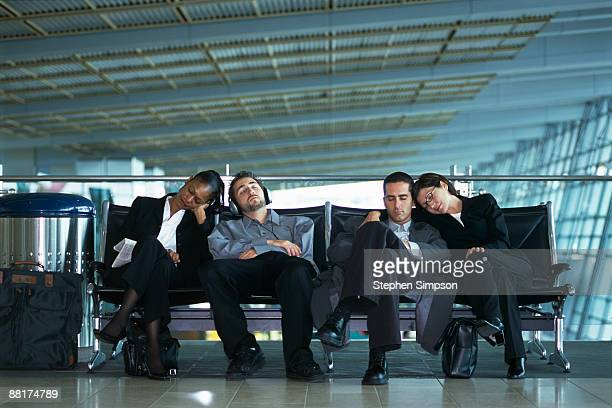 Businesspeople sleeping in airport terminal