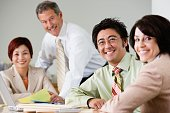 Businesspeople smiling at conference table
