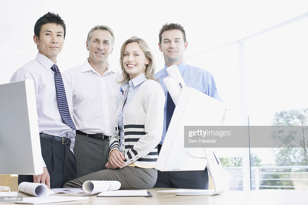 Businesspeople smiling at desk : Stock Photo