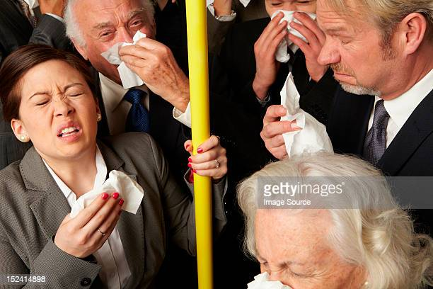 Businesspeople sneezing on subway train