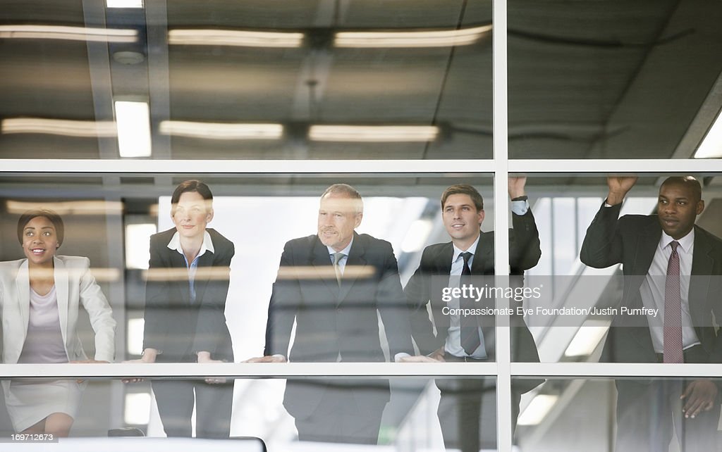 Businesspeople standing by glass wall in office : Stock Photo