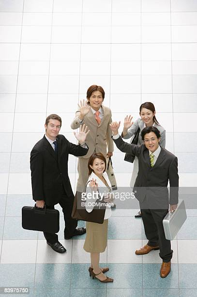 Businesspeople standing in circle, waving at camera, view from above