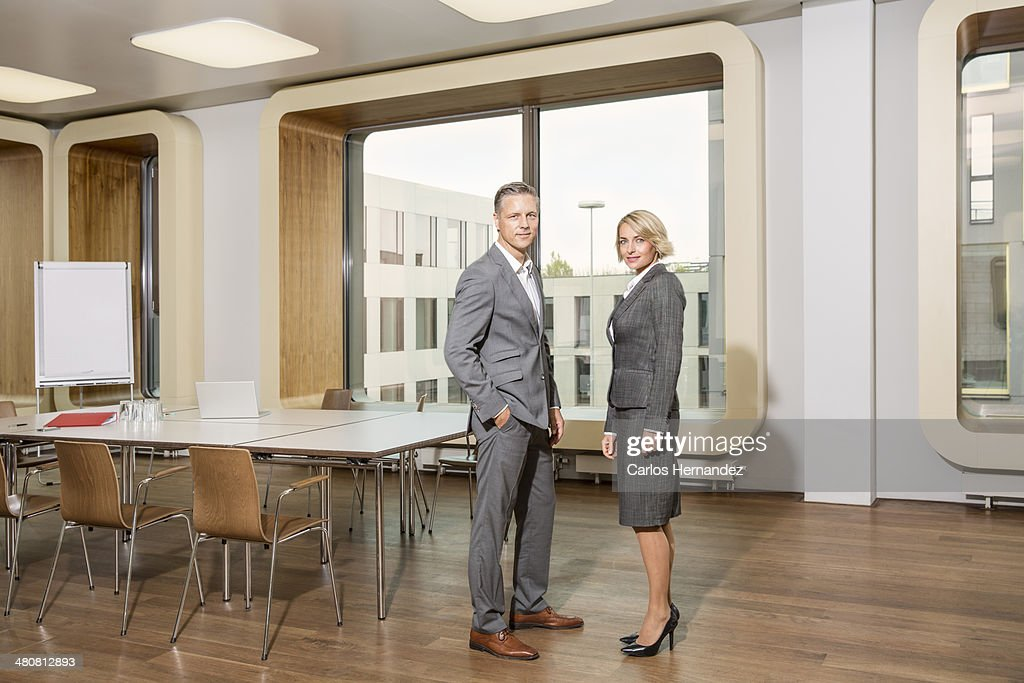 Businesspeople standing in conference room : Stock Photo