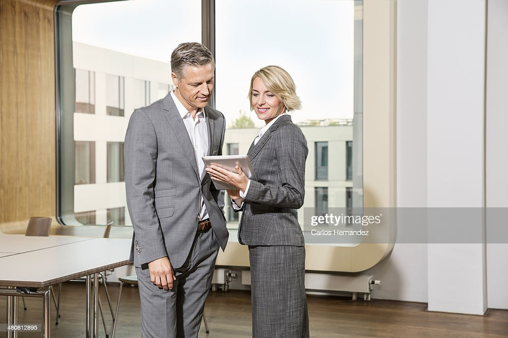 Businesspeople standing in conference room, using digital tablet : Stock Photo