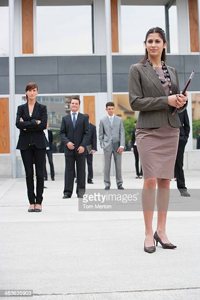 Businesspeople standing in office building courtyard