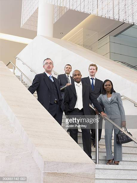 Businesspeople standing on stairway, smiling, portrait, low angle view