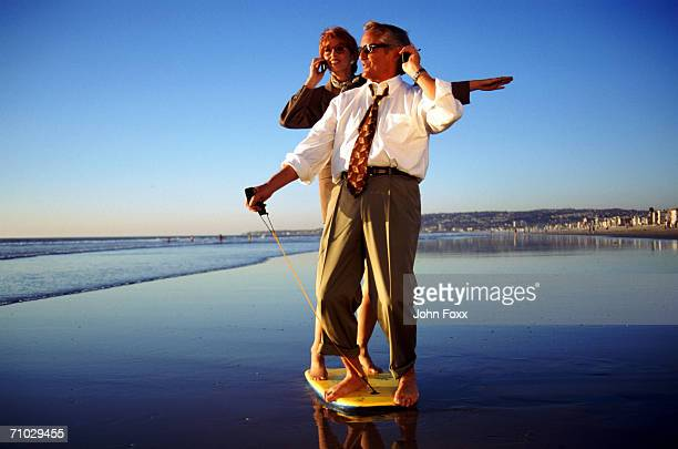 Businesspeople standing on surfboard using mobile phone on beach