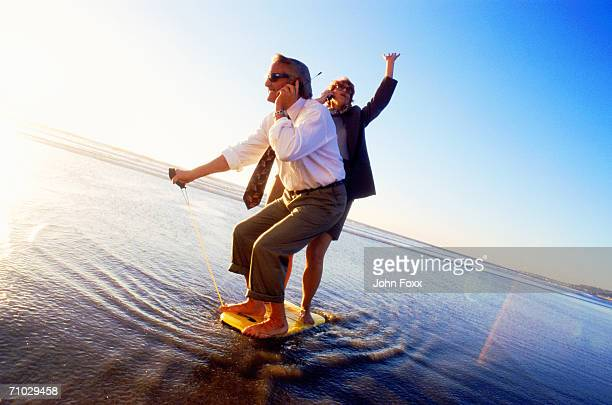 Businesspeople standing on surfboard using mobile phone