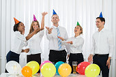 Group Of Businesspeople Standing Under Falling Confetti In Party