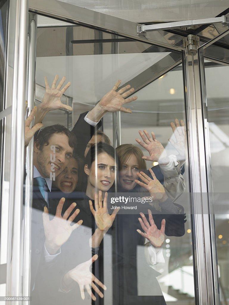 Businesspeople stuck in revolving door : Stock Photo