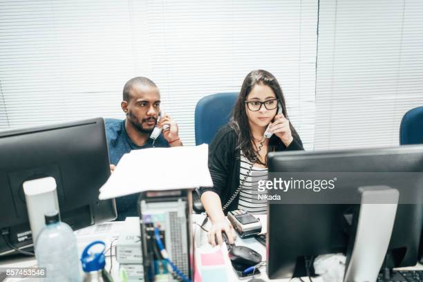 Geschäftsleute, die am Telefon im Büro sprechen