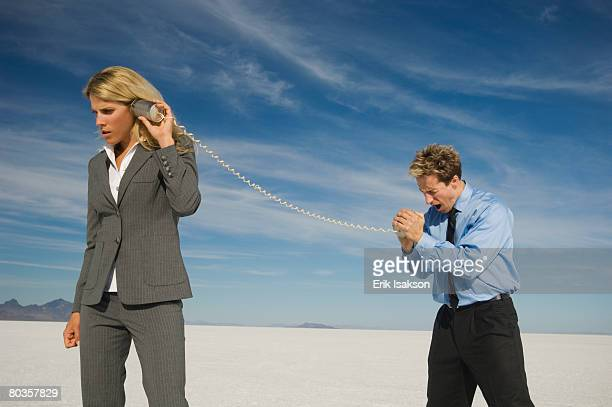 Businesspeople talking with can and string phone, Salt Flats, Utah, United States
