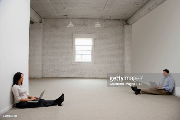 Businesspeople typing on laptops in empty room