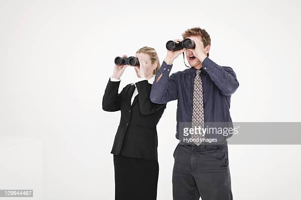 Businesspeople using binoculars