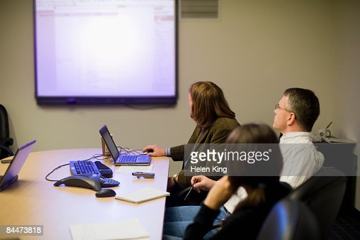 Businesspeople Using Laptops and Projector During Meeting : Stock Photo