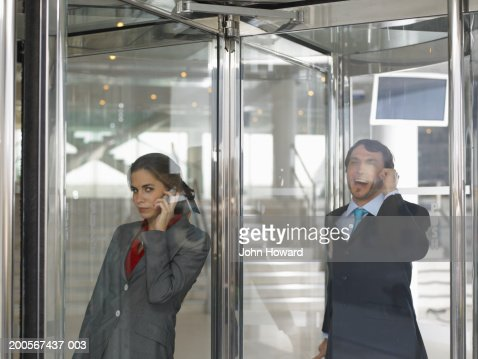Businesspeople using mobile phone in revolving door : Stock Photo