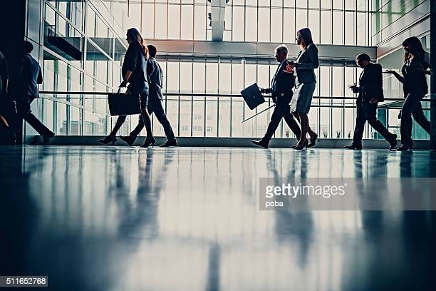 Businesspeople walking in busy office building