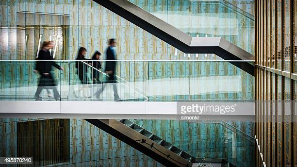 Businesspeople walking in office, blurred motion