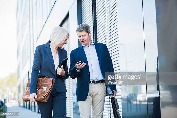 Businesspeople walking in street checking smart phone