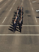 Businesspeople walking in unison on road, elevated view