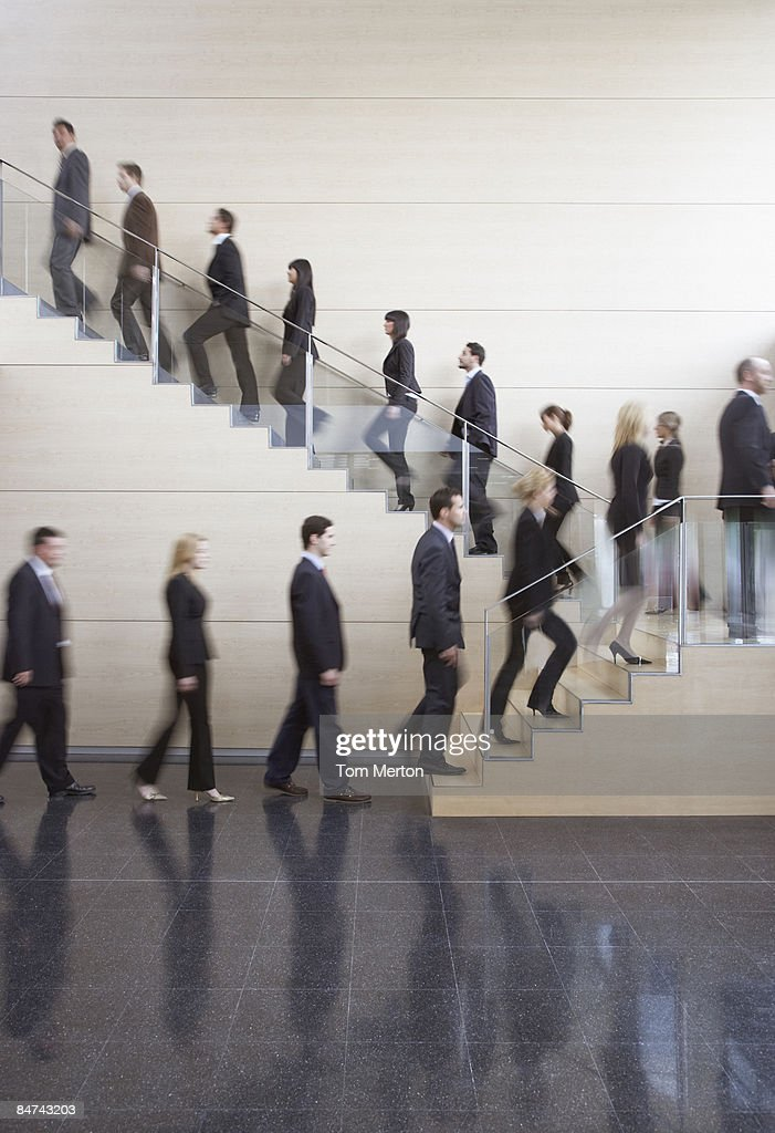 Businesspeople walking on office staircase : Stock Photo