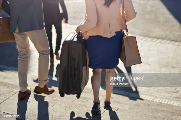 Businesspeople walking on staircase with bags