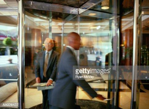 Businesspeople Walking Through a Revolving Door : Foto de stock