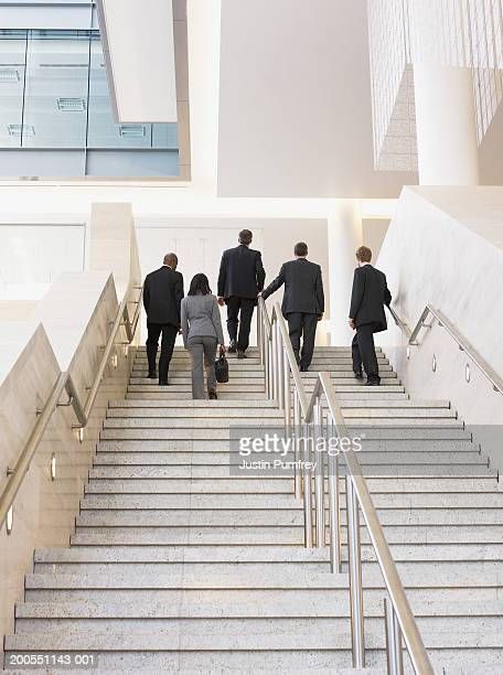 Businesspeople walking up stairs in office, rear view