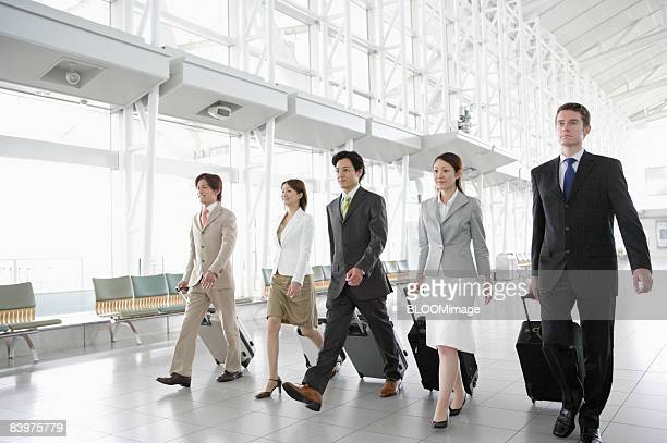 Businesspeople walking with suitcases