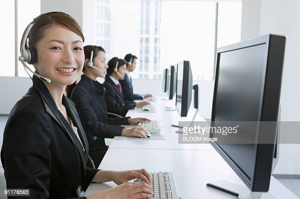 Businesspeople wearing headsets, using PC