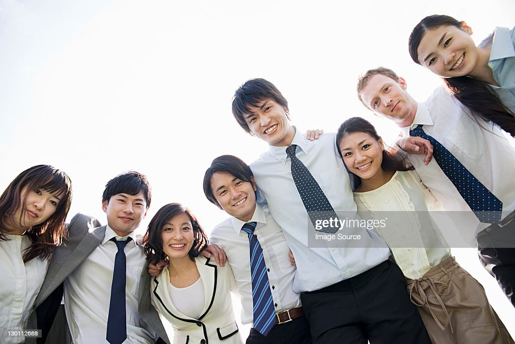 Businesspeople with arms around each other : Stock Photo