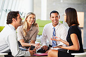 Businesspeople With Digital Tablet Having Meeting In Office Smiling