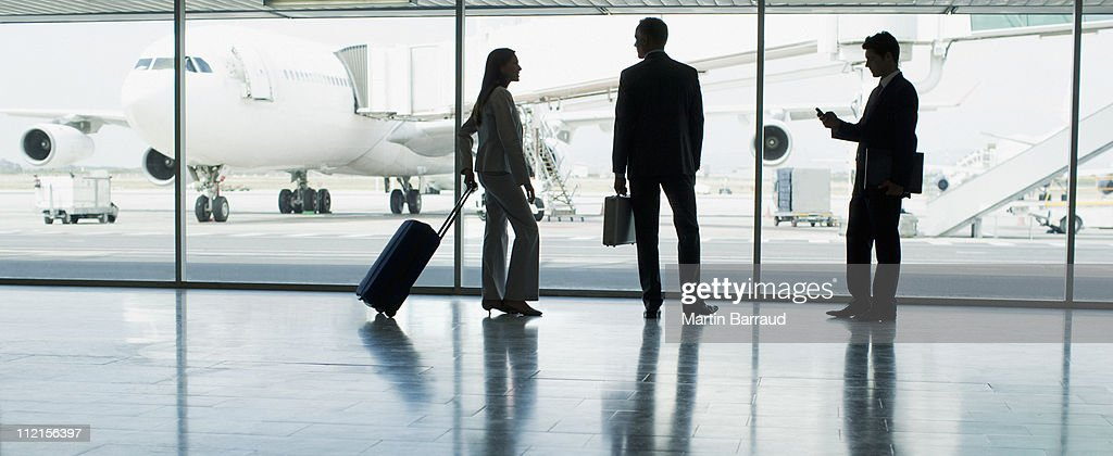 Businesspeople with suitcase in airport : Stock Photo