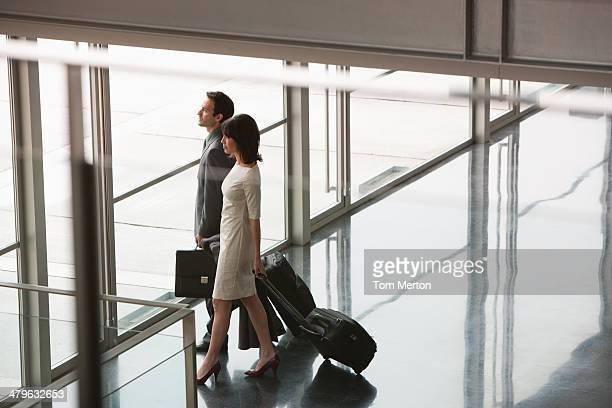 Businesspeople with suitcases leaving building