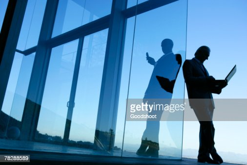 Businesspeople working by glass building : Stock-Foto