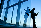 Businesspeople working by glass building