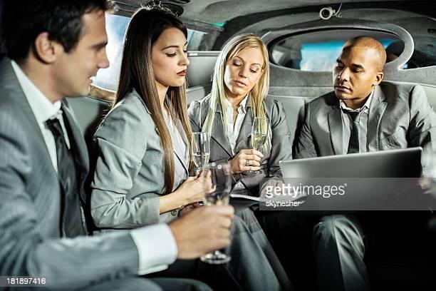 Hommes d'affaires travaillant dans un service de transport en limousine et de boire du champagne