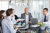 Business man passing over documents to leader during meeting. Businessman passing necessary agreement to the business partner in conference room. Group of businessmen and businesswomen working togethe