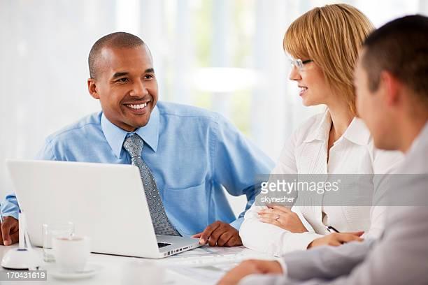 Hommes d'affaires travaillant sur ordinateur portable dans un bureau.