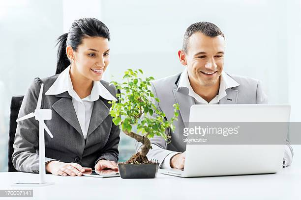 Businesspeople working together on laptop.