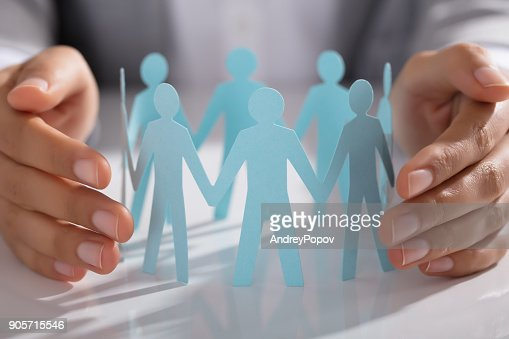 Businessperson Hand Protecting Paper Cut Out Figure On Table : Stock Photo