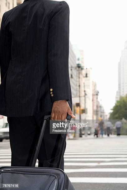 Businessperson rolling luggage down city street