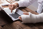Close-up Of A Businessperson's Hand With Hand Injury Using Laptop